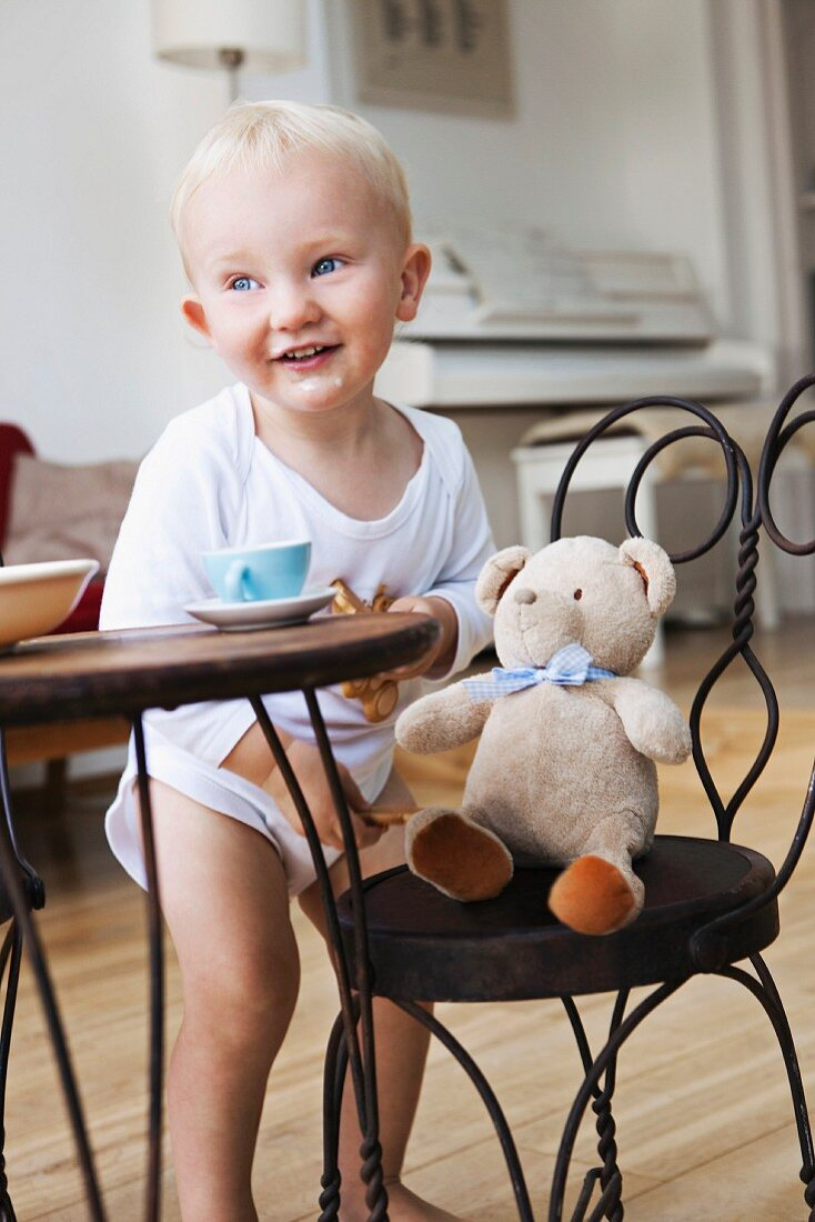 Boy toddler at tea party with his teddy