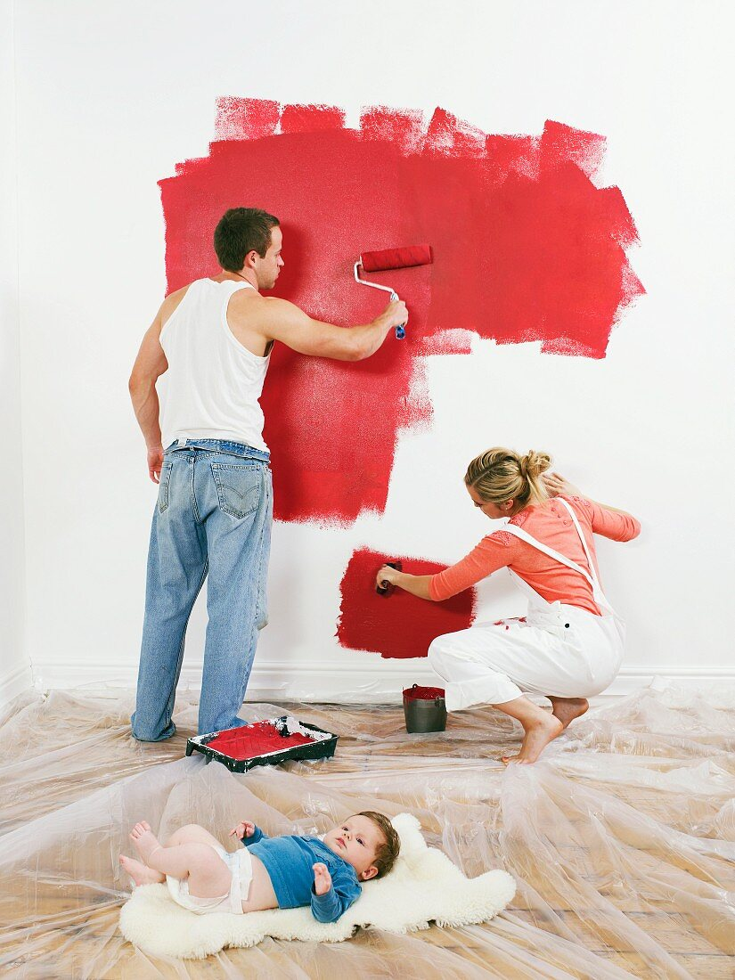 Couple painting a wall, baby on floor