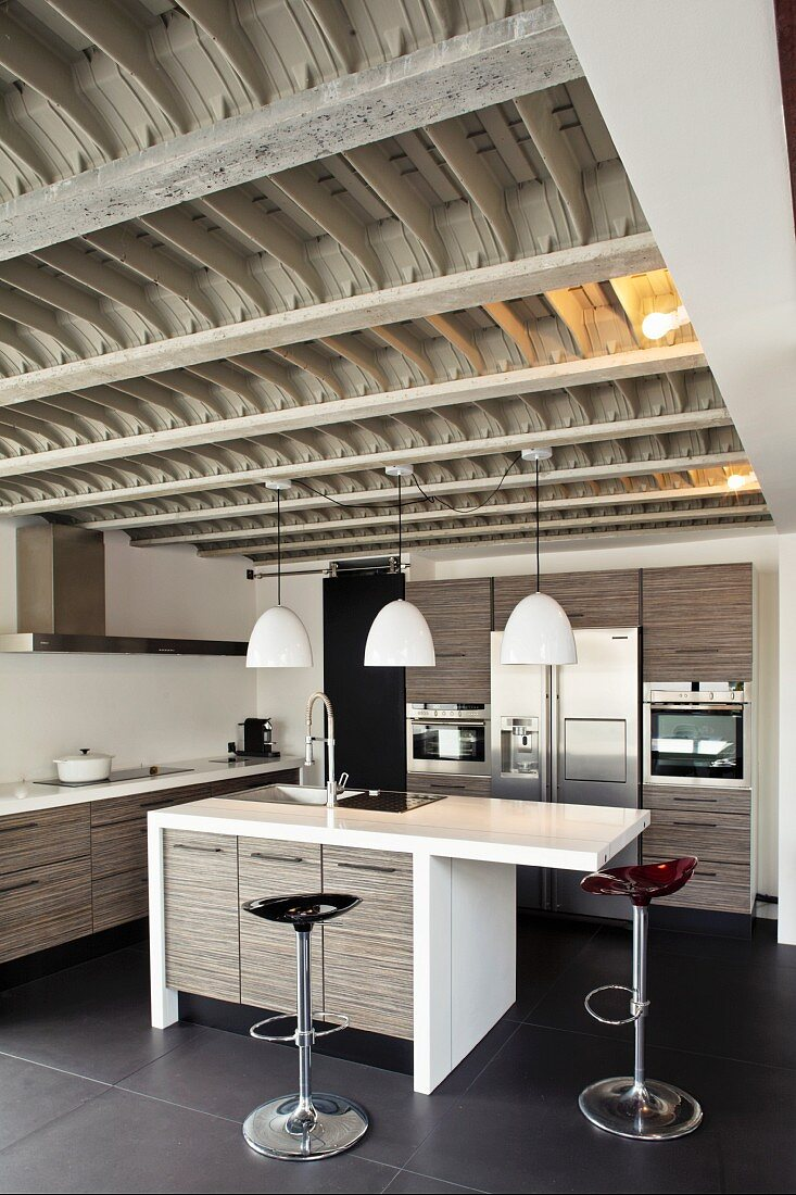 Modern designer kitchen with gray wooden kitchen units under a unique, wood and steel ribbed ceiling with an industrial look