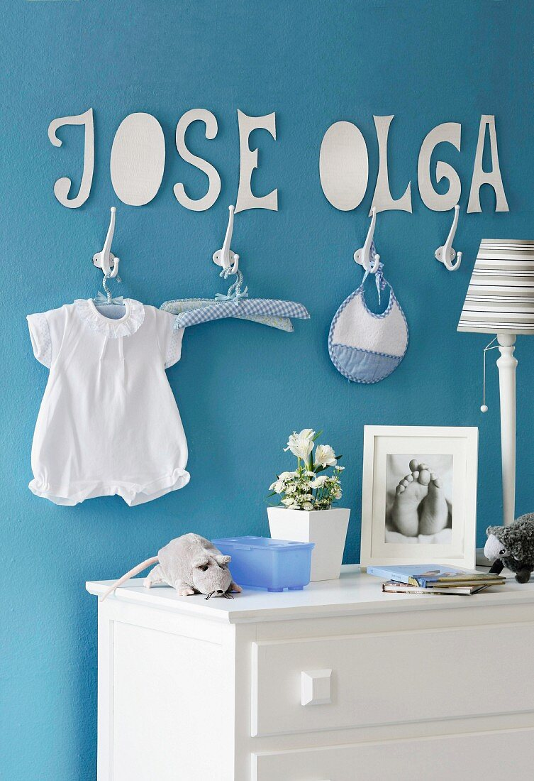 Baby's room with blue wall and cardboard baby name wall hanging above white hooks