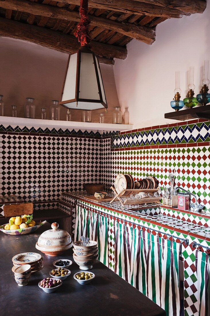 Corner of Oriental kitchen with mosaic-tiled sink unit and walls; shelves of oil lamps and glass vessels form border between tiles and plain painted walls; full bowls on wooden table in foreground