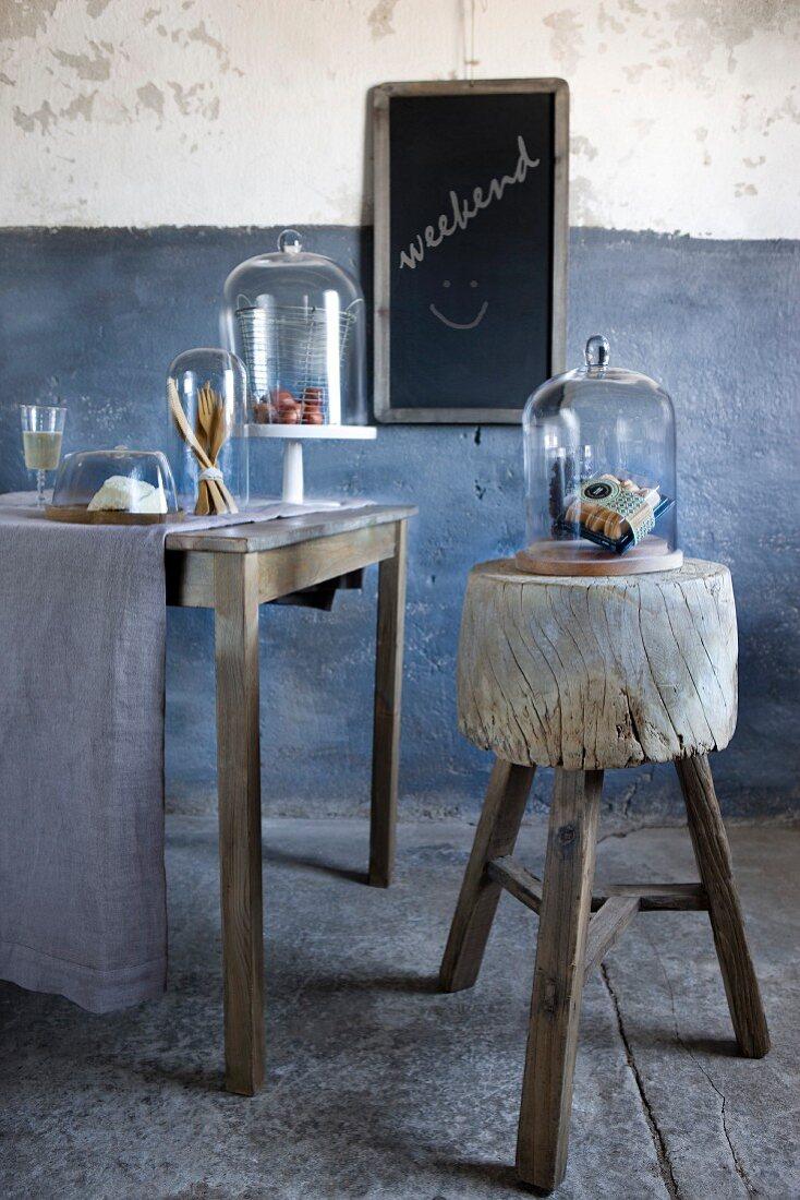 Verschiedene Lebensmittel unter Glasglocken auf Tisch; daneben ein rustikaler Holzblock