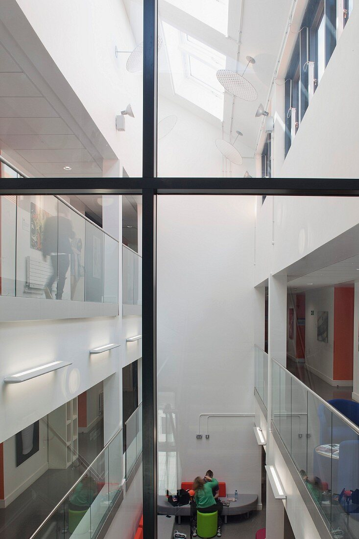 View through a glass stairwell into an atrium of a college with modern design with a skylight and see through balustrades (Oxford and Cherwell Valley College)