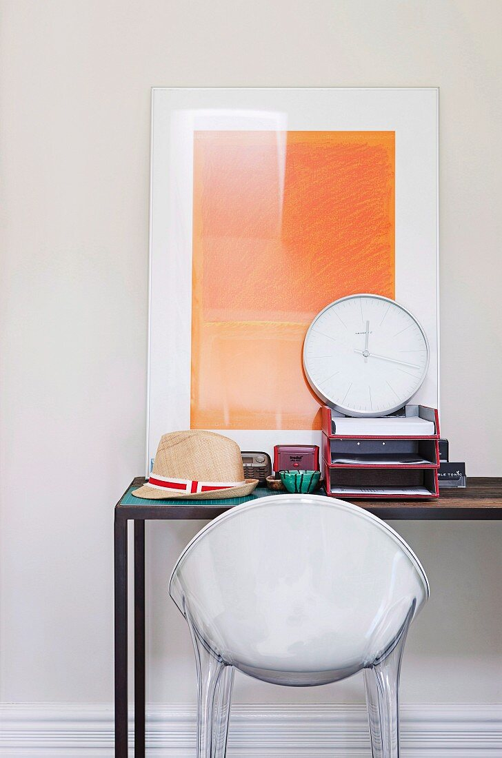 White plastic shell chair at desk with modern artwork leaning on wall