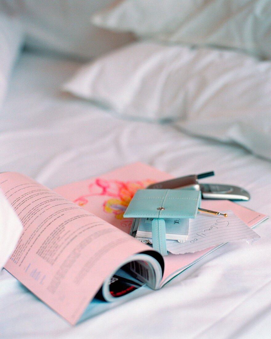 Zeitschrift, Notizbuch und Mobiltelefon auf einem Bett