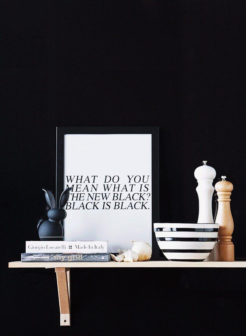 Kitchen utensils and framed motto on bracket shelf against black background
