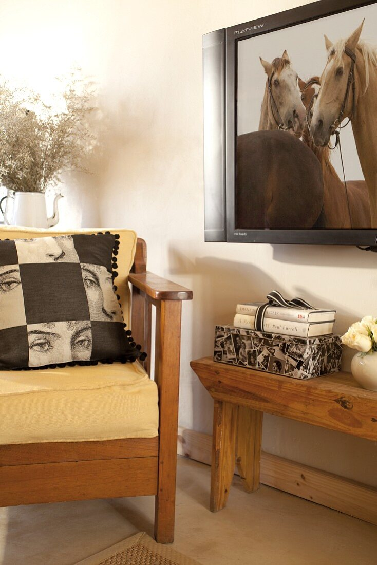 Wood-framed armchair with scatter cushion on yellow seat cushion next to wooden bench and wall-mounted TV