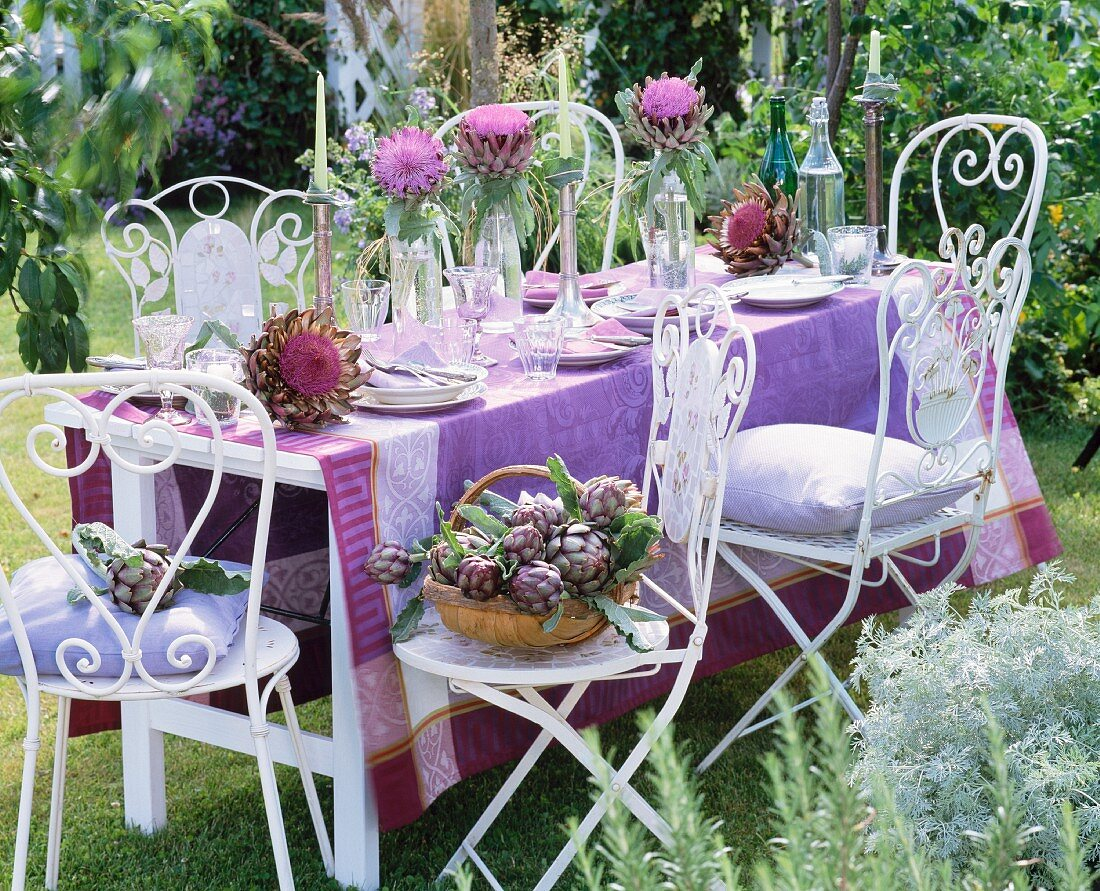 A table laid outside decorated with flowering artichokes and a purple cloth