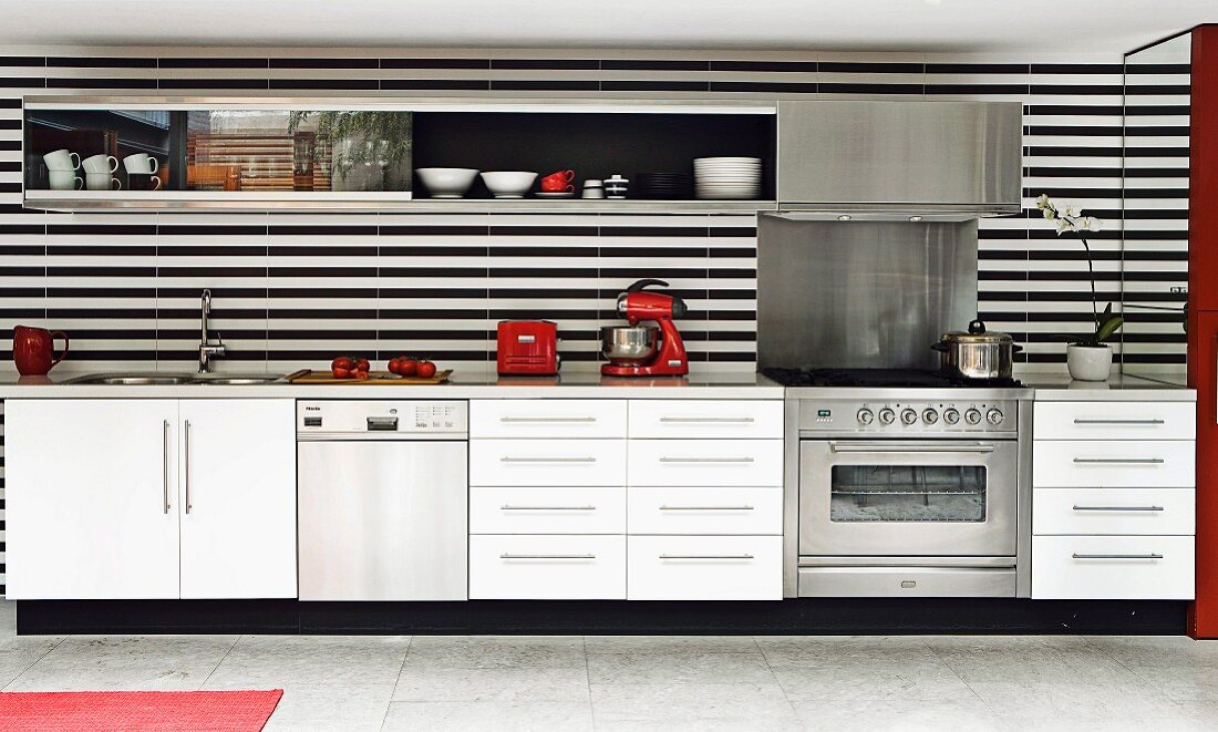 White, modern kitchen counter with black and white striped rear wall, mirrored wall at one end and red kitchen appliances