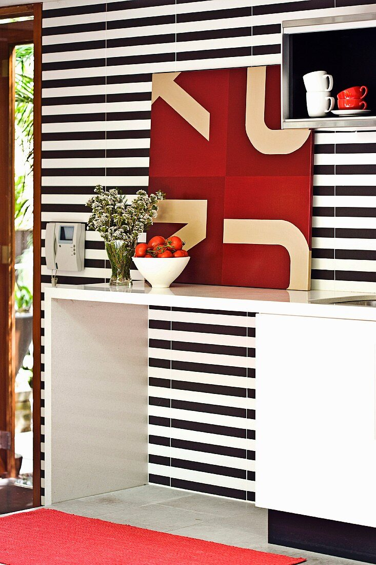 White fitted kitchen with black and white striped wall