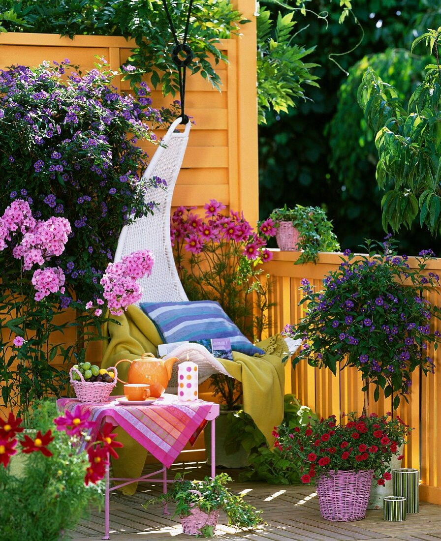 Comfortable hanging chair on balcony with colourful flowering plants