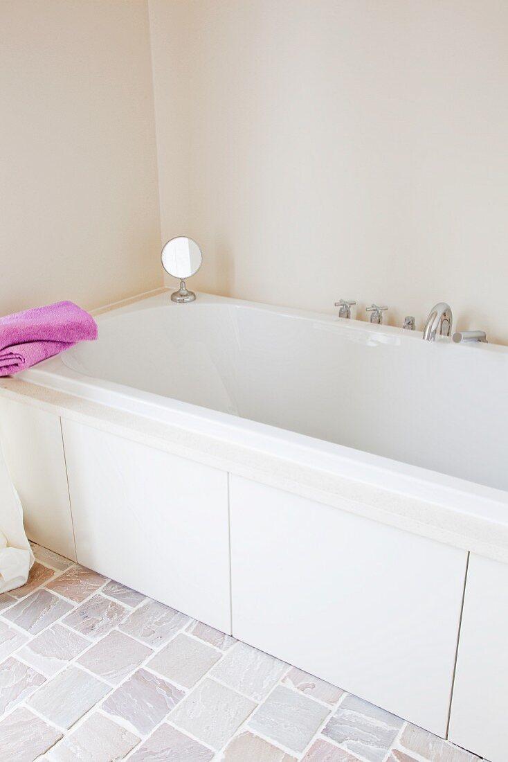 Badewanne in hellem, naturfarbenen Badezimmer mit Steinboden; zwei pinkfarbene Handtücher setzen einen fröhlichen Akzent
