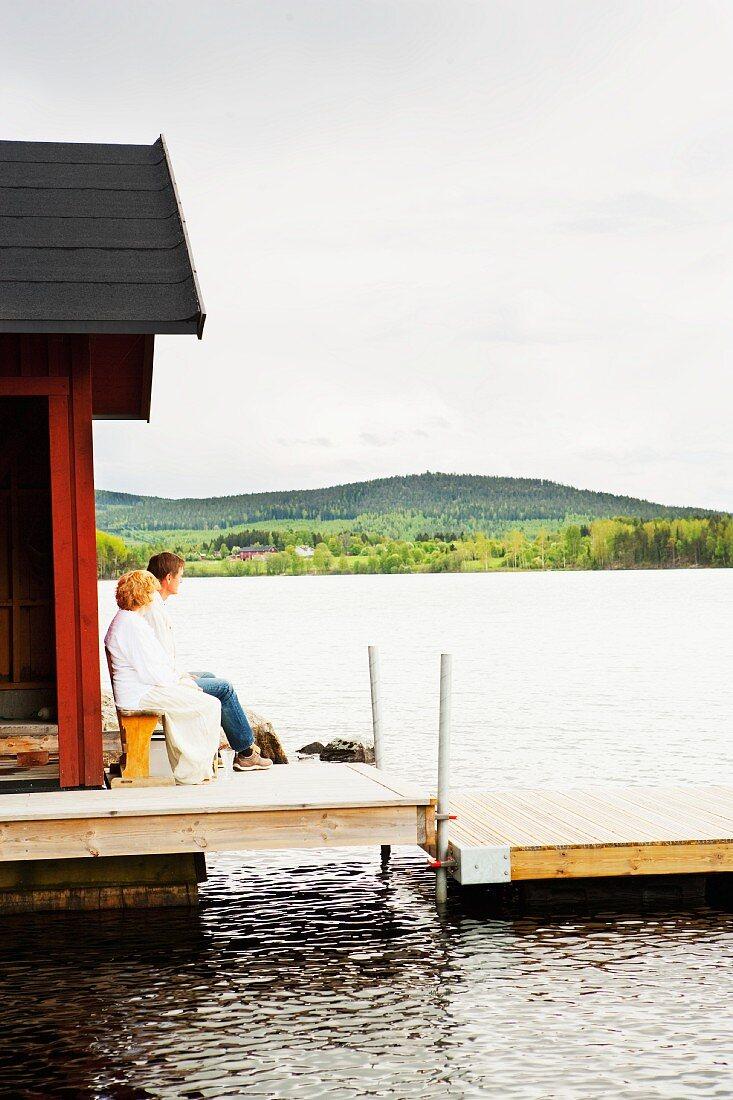 Couple enjoying the evening sun outside a boat house