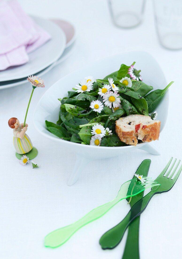 Grünes Plastik Besteck und Mädchenfigur neben Schale mit Spinatsalat und Gänseblümchen