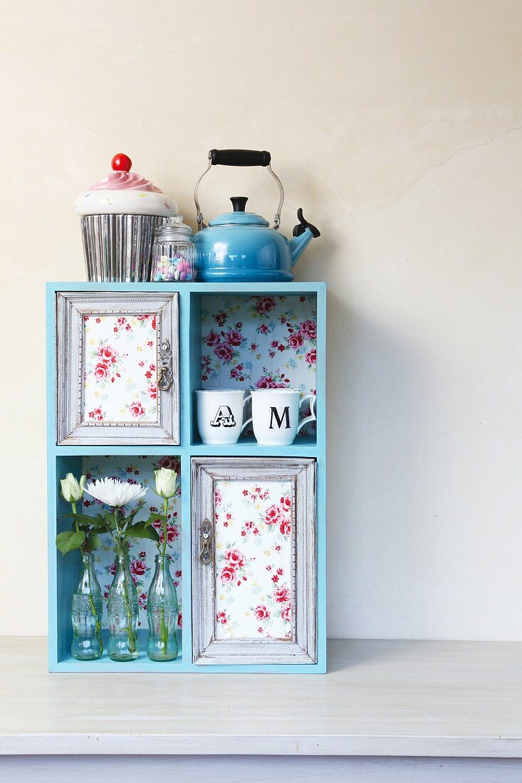 Decorative idea for simple shelf: floral fabric, cups, flowers in glass bottles and old picture frames create a whole new look