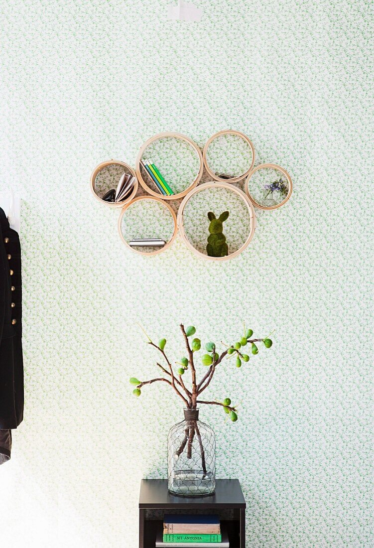 Bamboo steamers covered in wallpaper and mounted on wall as small shelves above branches of figs in glass bottle