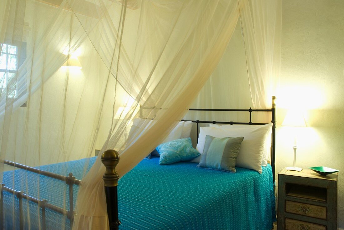 Transparent fabric canopy above double bed with vintage metal frame in Mediterranean bedroom