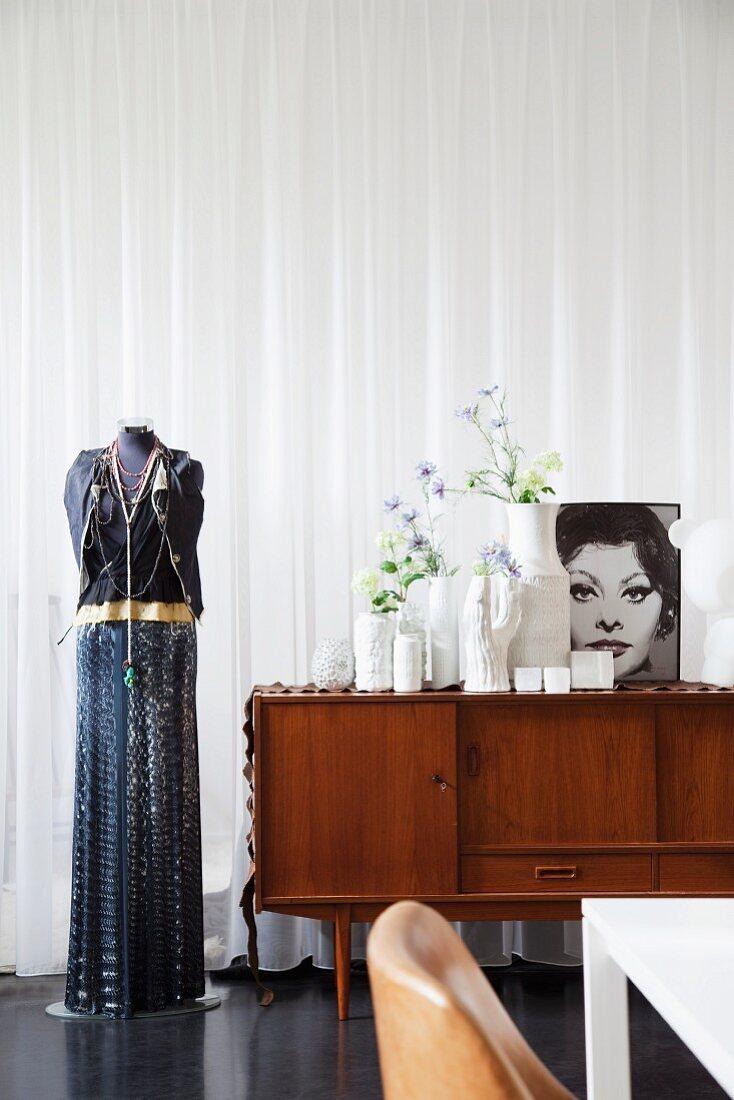 Schneiderpuppe in Abendkleidung neben 50er Jahre Sideboard mit Vasen und schwarzweissem Frauenportrait