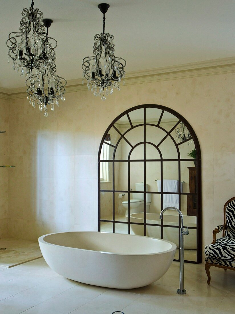 Free-standing, designer bathtub with standpipe tap fitting and chandeliers in front of large, arched lattice mirror