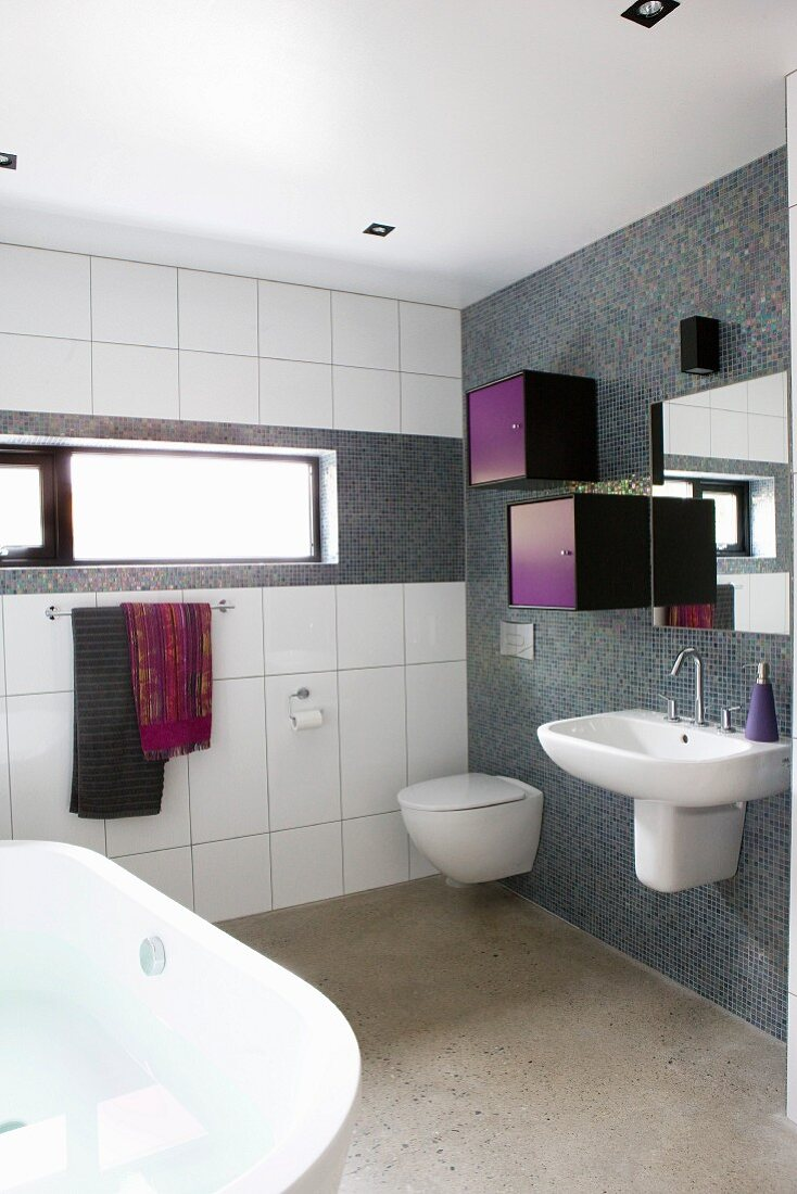Modern bathroom with washstand and small colourful cabinets mounted on wall with grey mosaic tiles