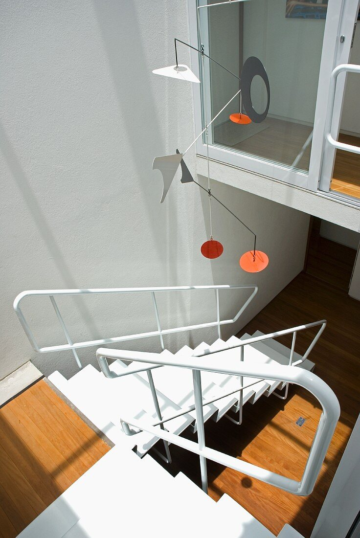 Mobile in style of Alexander Calder above interior staircase in white-painted metal