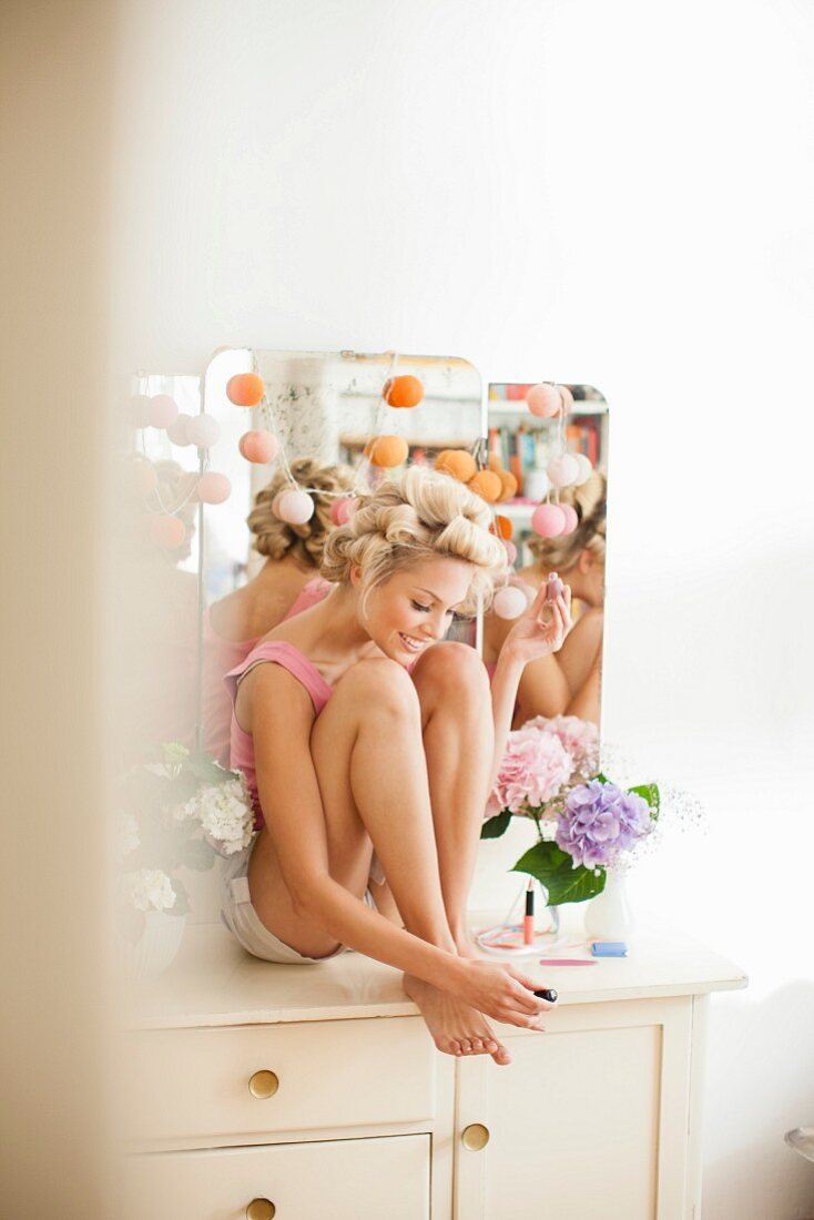 Blonde woman sitting on dressing table painting toenails