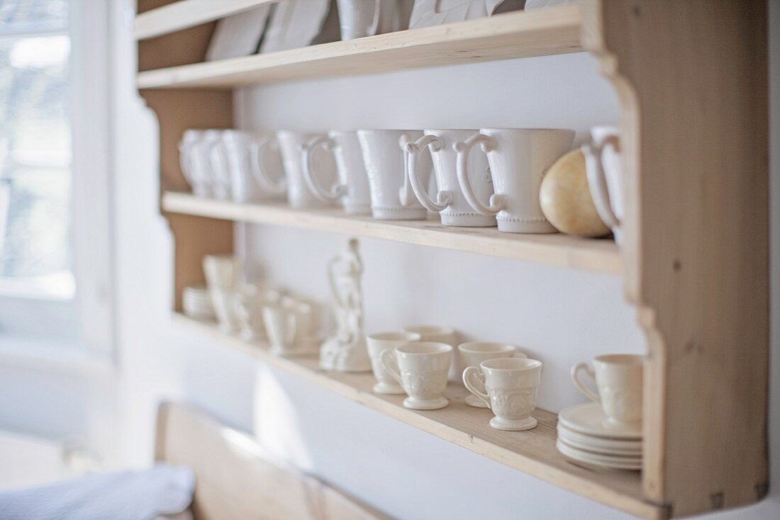 White teacups, saucers and china ornament on kitchen dresser