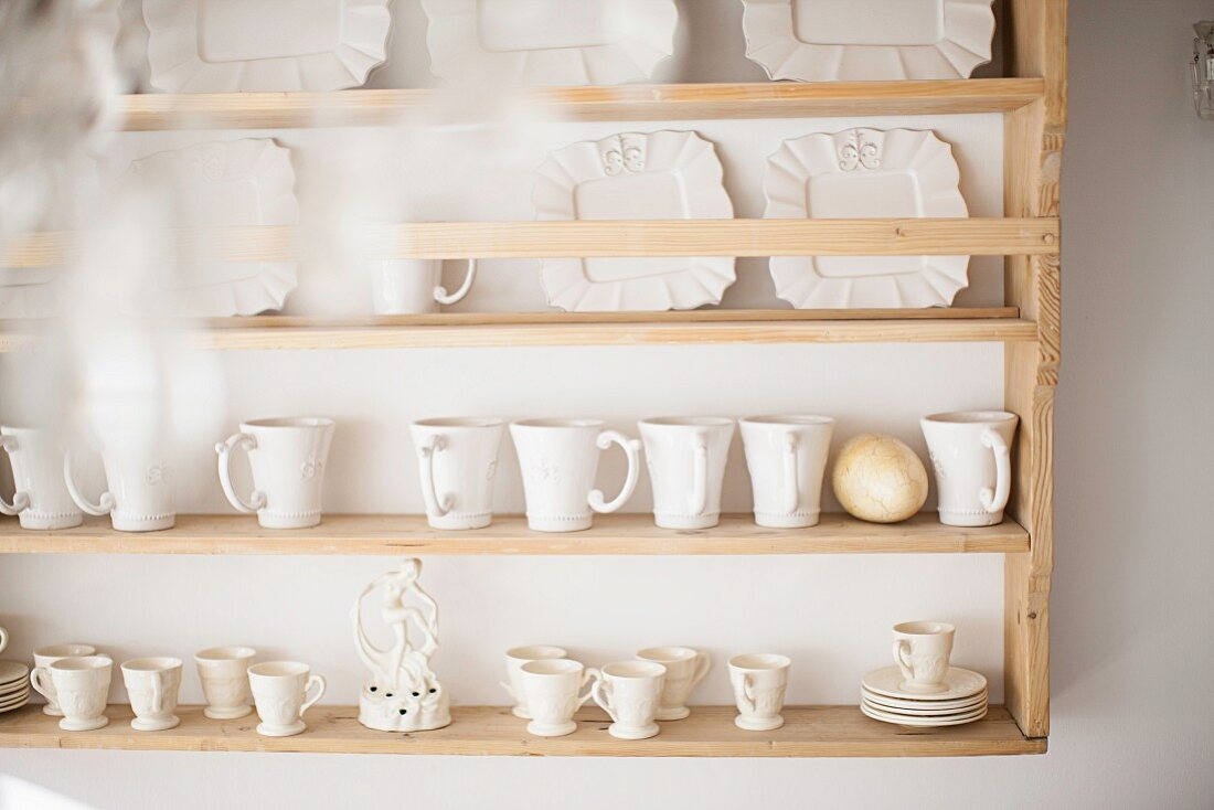 White teacups, plates and china ornament on kitchen dresser