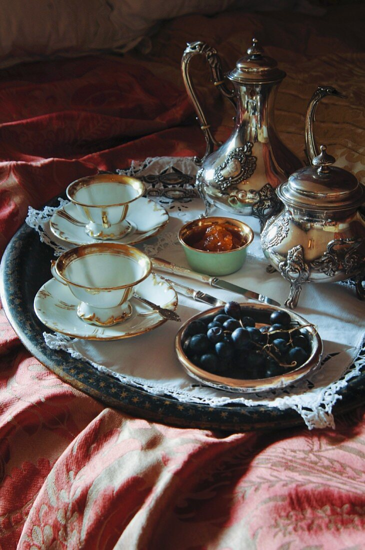 Breakfast tray on bed with silver Rococo pots, gold-rimmed china cups and grapes