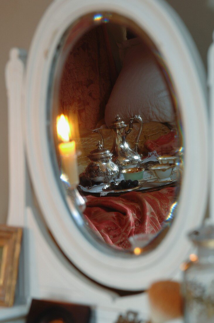 Breakfast tray with antique silver pots on bed reflected in mirror of dressing table