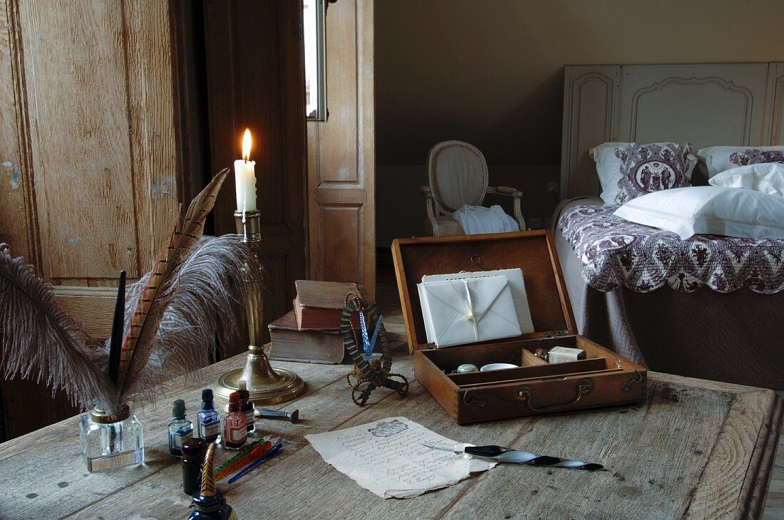 Old table in bedroom stylishly decorated with quill pens, silver candlestick and open stationary case