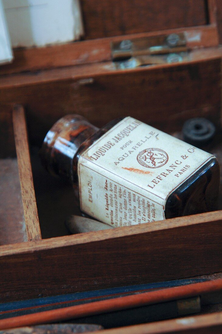 Old bottle of water colour paint with French label in wooden box