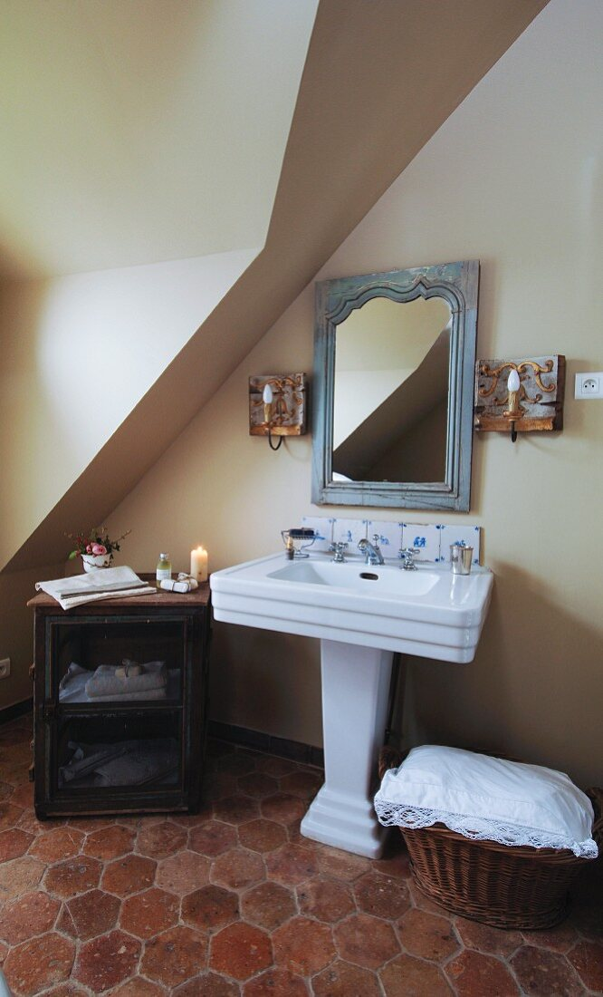 Collection of antiques around French pedestal washbasin; honeycomb patterned terracotta floor tiles