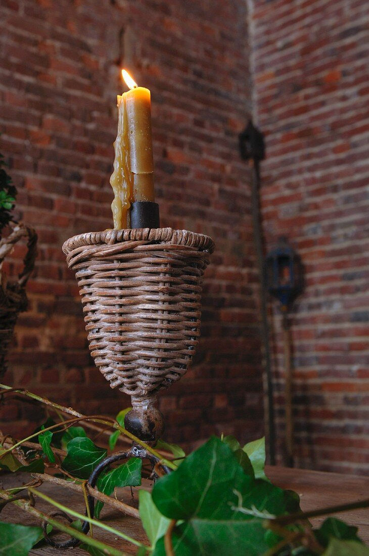 Lit candle in metal and wicker candlestick on table in front of interior corner with exposed brick walls