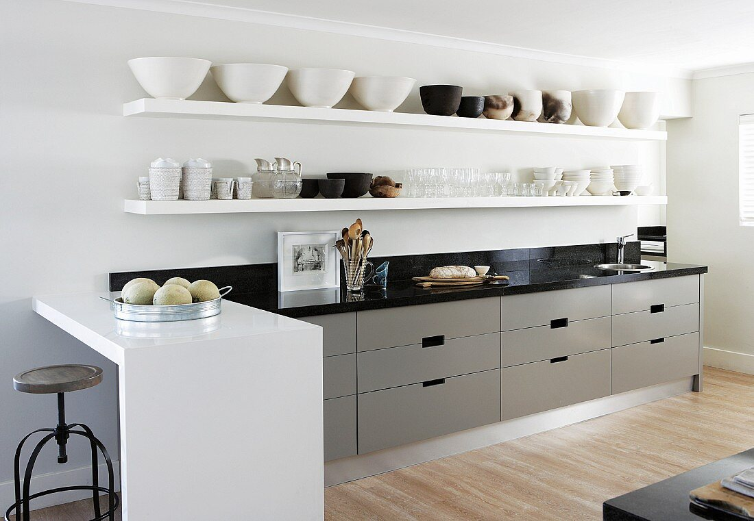 Bowls on white floating shelves above kitchen counter with grey units in open plan modern designer kitchen