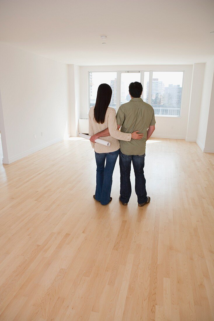 Rear view of couple with blueprints in empty room