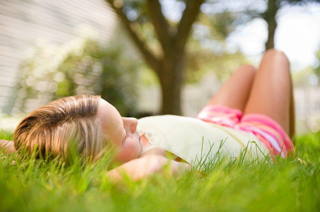 USA, New York, Girl (10-11) relaxing in park