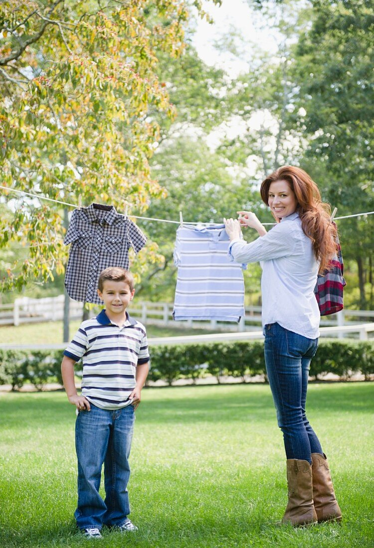 USA, New York, Flanders, Mother and son (8-9) doing laundry