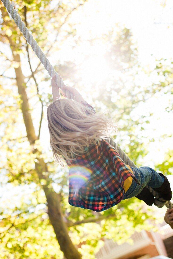 USA, Utah, rear view of girl (6-7) hanging on rope