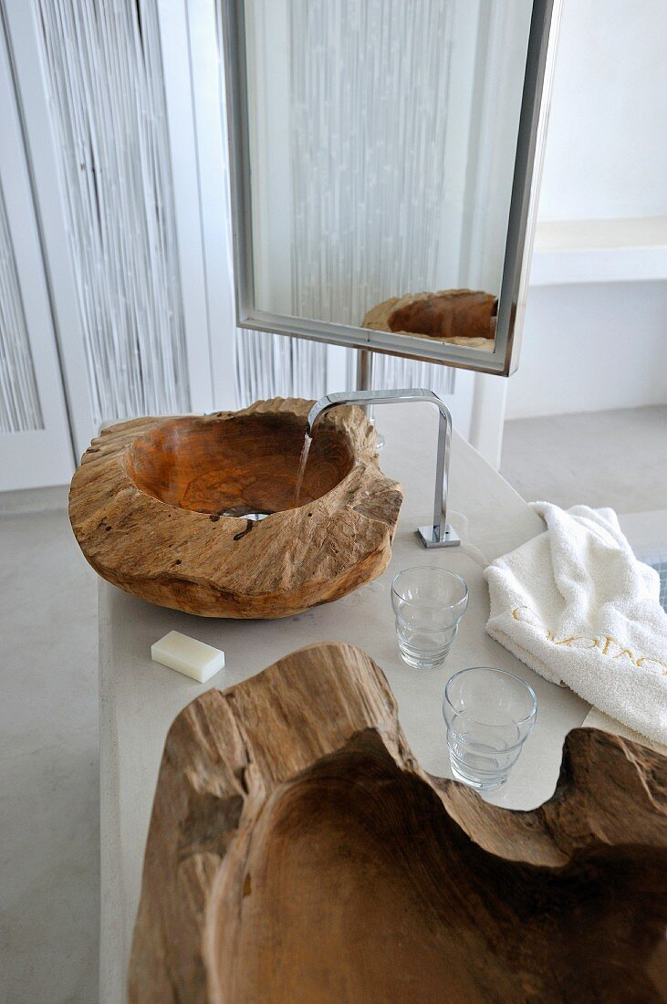 Full-length mirror behind washstand with basins made from solid, craggy wooden blocks with polished interiors