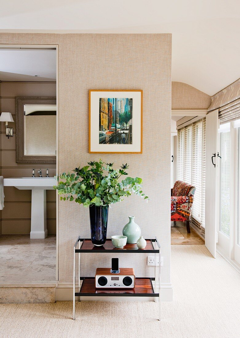 Bouquet on console table below modern painting on wall with natural fibre wallpaper next to open bathroom door