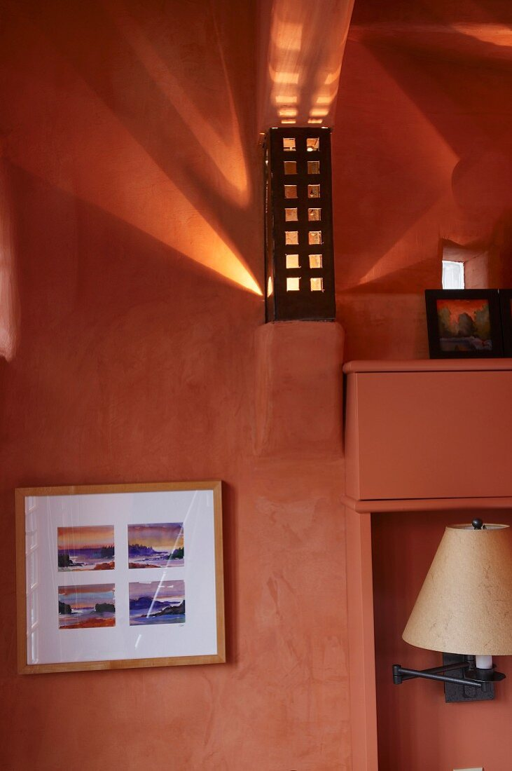 Framed picture below sconce lamp on wall bracket with perforated metal lampshade throwing dramatic pattern of light and shade onto salmon pink wall