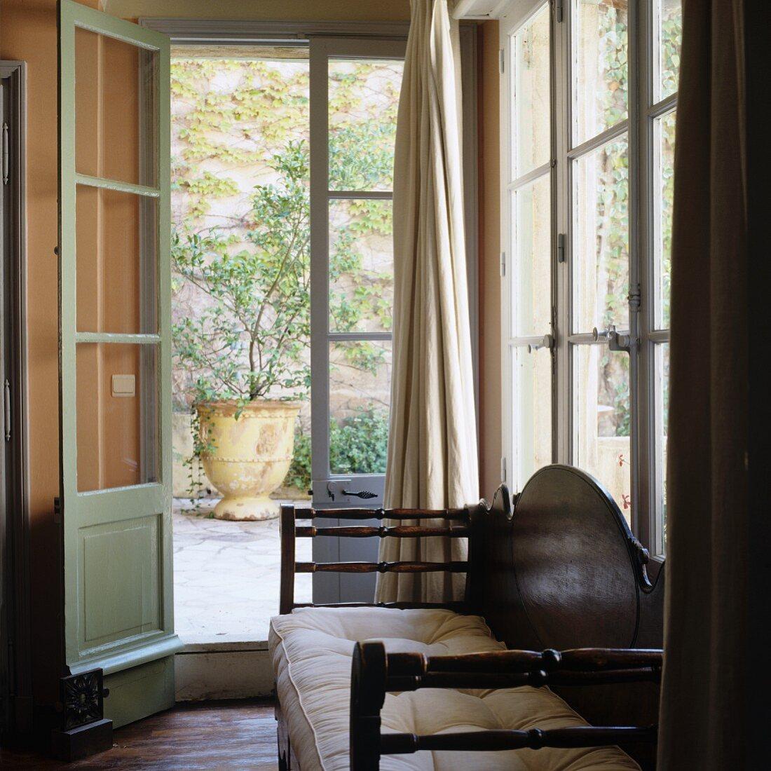 Antique wooden bench with seat cushions in window niche with door leading to Mediterranean terrace