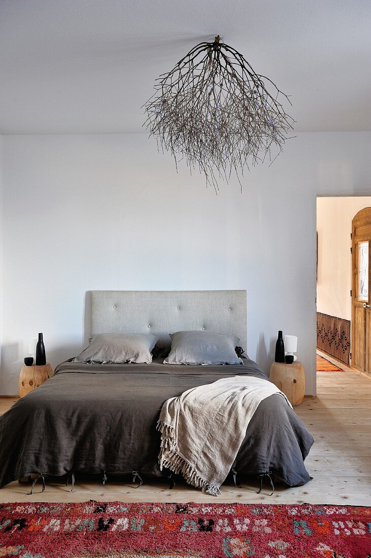 French bed with bedding in warm gray tones, red wool rug and lampshade made of dried branches to create a natural look