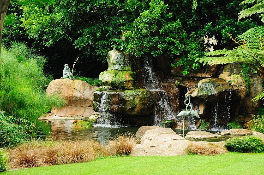 Affenfigur und verschlungene Flamingoskulpturen in einer mit Steinformationen und Grünpflanzen naturnah angelegten Wasserlandschaft