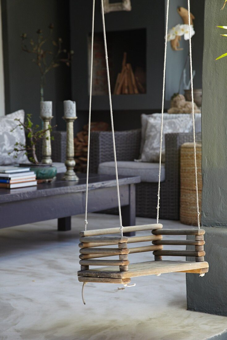 Child's swing hung between dark coffee table and wicker armchair in living room