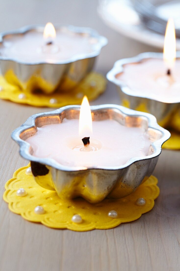 Small cake moulds used as tealights on doilies