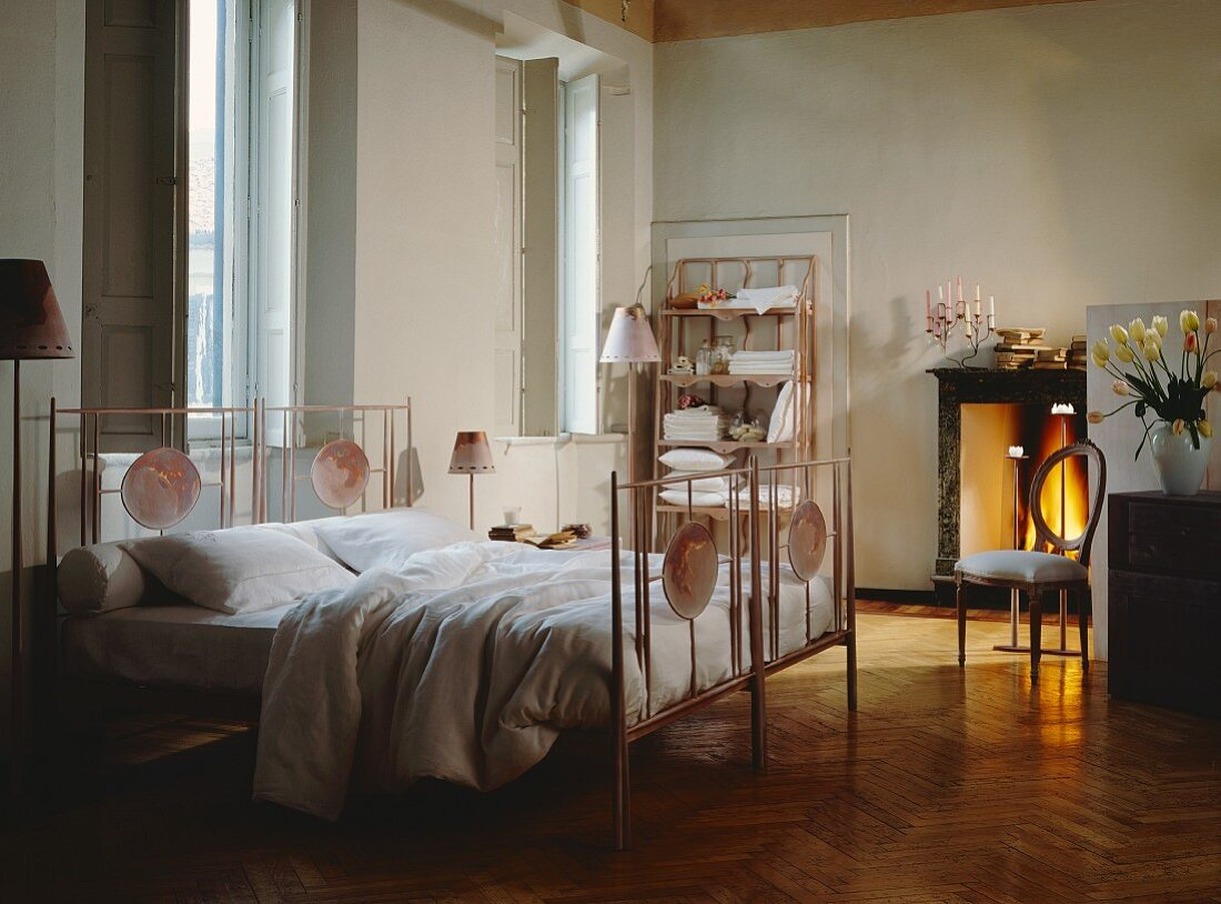 Traditional bedroom with tall windows and large metal bed with painted oval panels; firelight from open fireplace in background