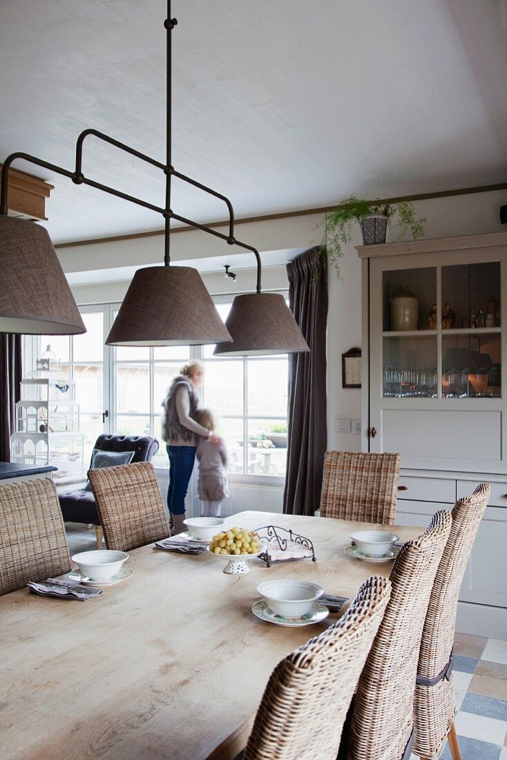 Set oak table, wicker chairs and country-house pendant lamp; mother and child in front of terrace windows in background