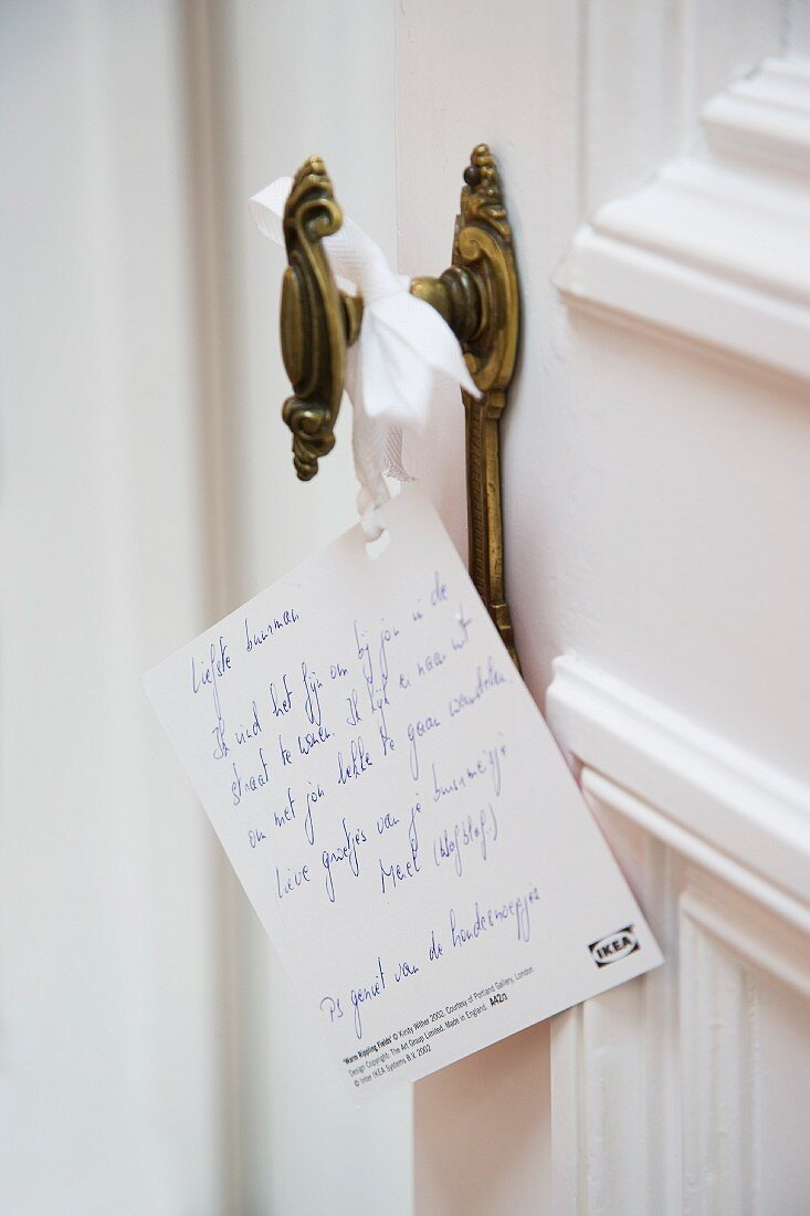 Card with hand-written greeting hanging on vintage interior doorknob